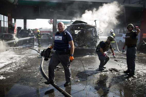 Israeli police explosive experts survey the scene at a petrol station after it was hit by a rocket in the southern city of Ashdod July 11, 2014. REUTERS/Amir Cohen