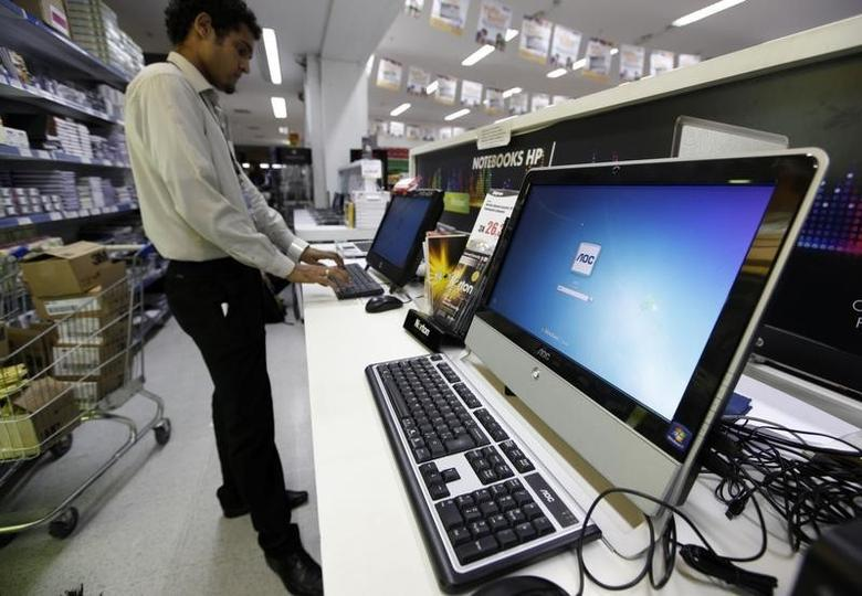 A Brazilian vendor types on a computer at a supermarket in Sao Paulo March 3, 2011. REUTERS/Nacho Doce
