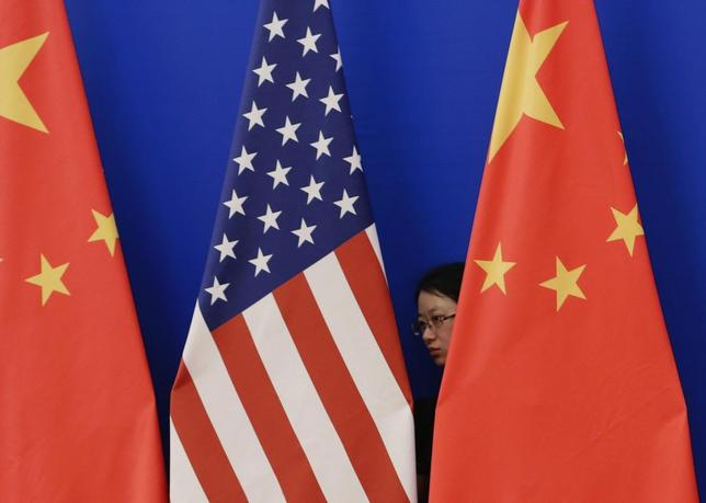 A member of staff from Chinese government adjusts U.S. and Chinese national flags before a news conference for the 6th round of U.S.-China Strategic and Economic Dialogue at the Great Hall of the People in Beijing, July 10, 2014. REUTERS/Jason Lee