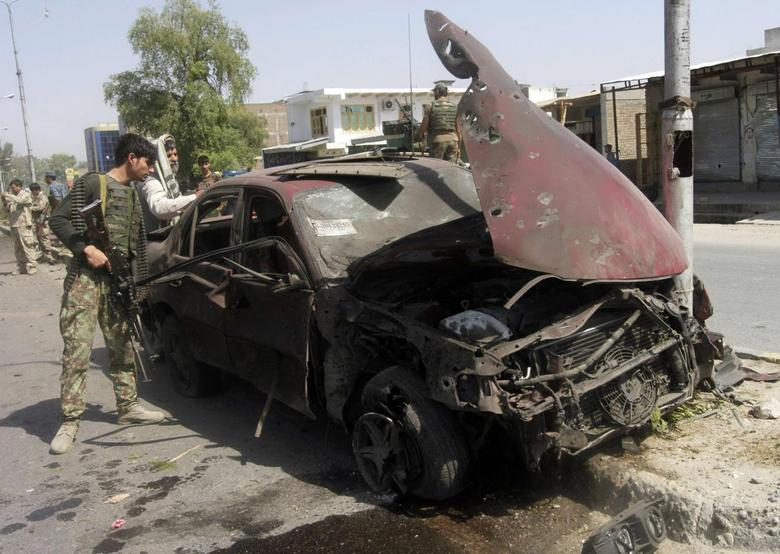 A member of the Afghan security force looks into a car, which was damaged after a blast in the eastern city of Jalalabad, in Nangarhar province July 12, 2014. REUTERS/Parwiz