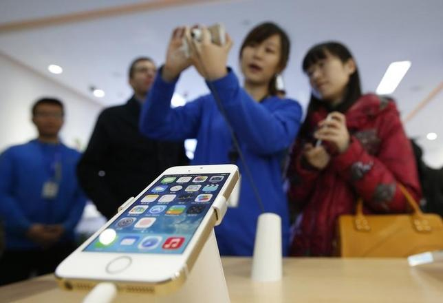 A staff of a China Mobile shop explains a function of the iPhone 5s to a customer in Beijing January 17, 2014.  REUTERS/Kim Kyung-Hoon