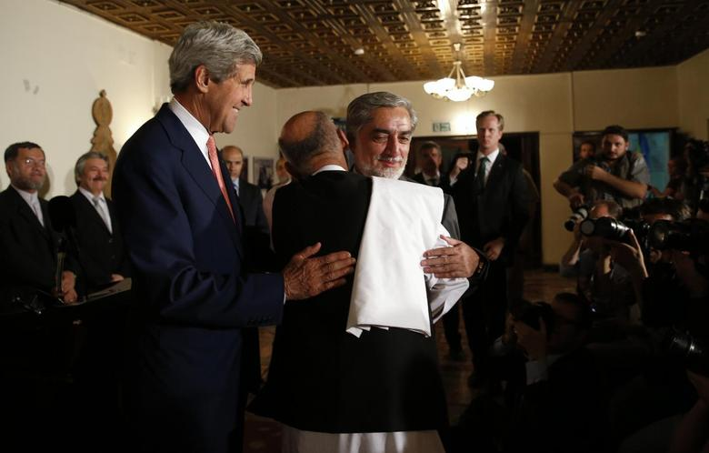 Afghanistan's presidential candidate Ashraf Ghani (C) and rival Abdullah Abdullah (R) hug in front of mediator U.S. Secretary of State John Kerry (L) after they announced a deal for the auditing of all Afghan election votes at the United Nations Compound in Kabul, late July 12, 2014. REUTERS/Jim Bourg