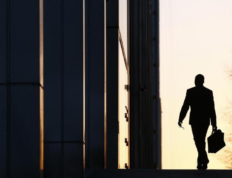 A worker arrives at his office in the Canary Wharf business district in London February 26, 2014.  REUTERS/Eddie Keogh
