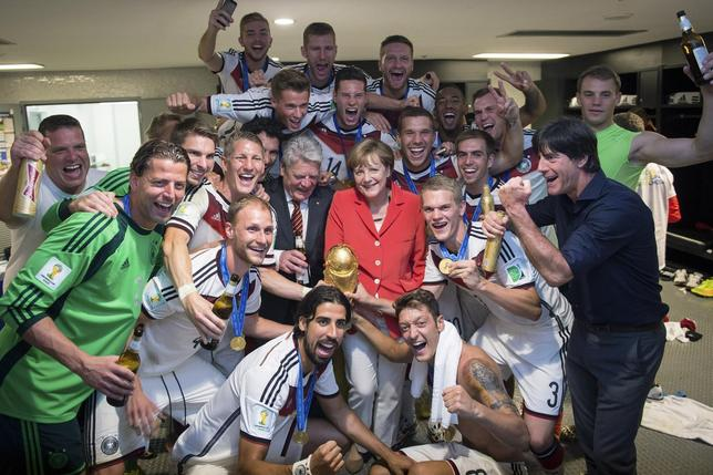 German Chancellor Angela Merkel (centre R) and German President Joachim Gauck (centre L) pose with the Germany's coach Joachim Loew (front R) and his players after Germany beat Argentina in the 2014 World Cup final at the Maracana stadium in Rio de Janeiro July 13, 2014.    REUTERS/Bundesregierung/Guido Bergmann/Handout via Reuters