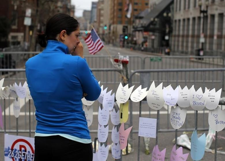 Allison Petrone cries while paying her respects to the victims of the Boston Marathon bombings at a memorial at the barricade surrounding the scene of the explosions in Boston, Massachusetts April 18, 2013.        REUTERS/Brian Snyder