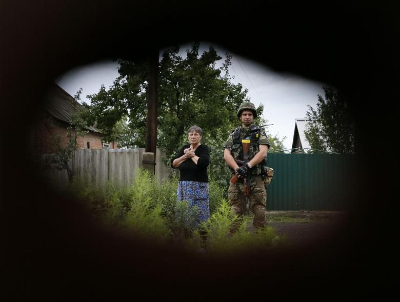 A member of the Ukrainian police special task force ''Kiev-1'' stands beside a local woman as sappers check her building in the eastern Ukrainian village of Semenovka, near Sloviansk, July 14, 2014. REUTERS/Gleb Garanich