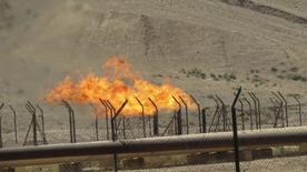 Нефтяное месторождение Bai Hassan близ Киркука, 12 июля 2014 года. Цены на нефть Brent снижаются, но держатся вблизи $107 за баррель из-за напряженной обстановки на Ближнем Востоке и в Северной Африке. REUTERS/Ako Rasheed