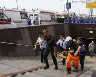 Спасатели выносят пострадавшего со станции метро в Москве 15 июля  2014 года. Не менее 19 человек погибли и 120 получили ранения в результате схода с рельсов трёх вагонов московского метро в утренний час пик вторника - очередной аварии в самой загруженной подземке планеты. REUTERS/Sergei Karpukhin