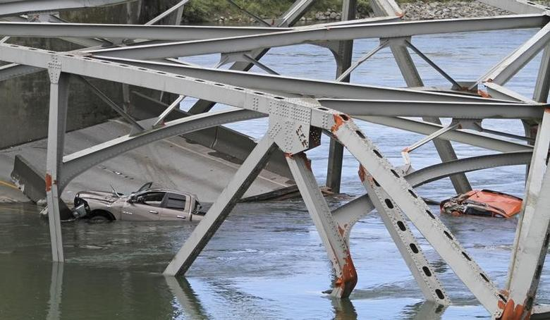 Cars are seen in the water as a span of highway bridge sits in the Skagit River May 24, 2013 after collapsing near the town of Mt Vernon, Washington late Thursday.  REUTERS/Cliff DesPeaux