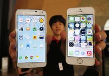 Un Galaxy 5 de Samsung Electronics et un iPhone 5S d'Apple. Le géant sud-coréen est en train de perdre des parts de marché sur les smartphones bas et haut de gamme au profit respectivement des fabricants chinois et d'Apple dont l'iPhone 6 est attendu en septembre, montre une étude. /Photo prise le 16 juilet 2014/REUTERS/Kim Hong-Ji