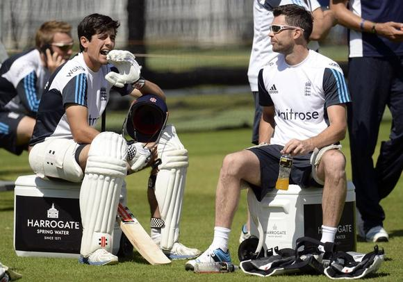 England's captain Alastair Cook sits with team-mate James Anderson (R) during a training session before Thursday's second cricket test match against India at Lord's cricket ground in London July 16, 2014.   REUTERS/Philip Brown