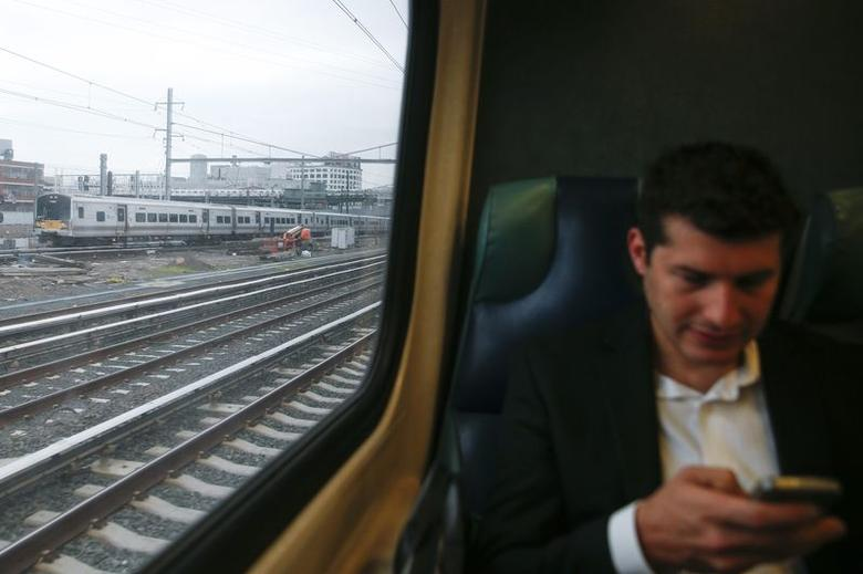 A Long Island Railroad makes its way out of Pennsylvania Station as a man uses his phone aboard a train in New York July 16, 2014. REUTERS/Shannon Stapleton