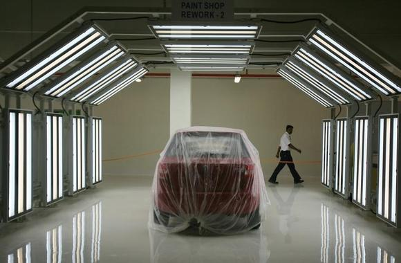 A worker walks past a new vehicle on the assembly line at the Volkswagen India Plant in Chakan, 160 km south-east of Mumbai March 31, 2009. REUTERS/Punit Paranjpe/Files