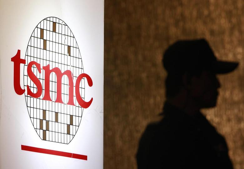 A security personnel stands near the logo of Taiwan Semiconductor Manufacturing Co. Ltd (TSMC) during an investor conference in Taipei, July 16, 2014.  REUTERS/Pichi Chuang