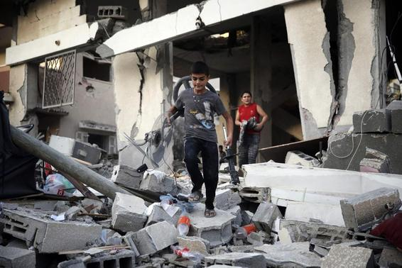 Palestinian boys salvage belongings from a damaged home, which police said was targeted in an Israeli air strike, in Gaza City July 17, 2014. REUTERS-Finbarr O'Reilly