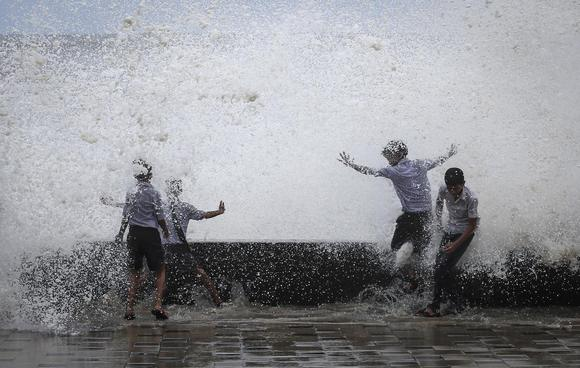 School boys get drenched in a large wave during high tide at a sea front in Mumbai July 14, 2014.  REUTERS/Danish Siddiqui