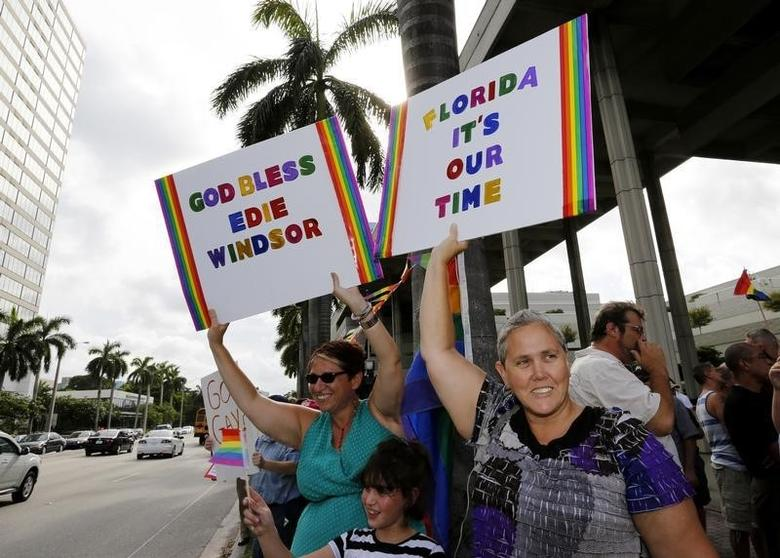 Heidi Schfran (L) and Marlene Marante of Wilton Manors hold signs at a rally by gay rights activists following the U.S. Supreme Court's 5-4 ruling, striking down as unconstitutional the Defense of Marriage Act (DOMA), in Fort Lauderdale, Florida June 26, 2013.   REUTERS/Joe Skipper