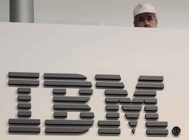 A worker is pictured behind a logo at the IBM stand on the CeBIT computer fair in Hanover February 26, 2011.  REUTERS/Tobias Schwarz