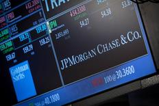 A screen displays JP Morgan Chase & Co. on the floor of the New York Stock Exchange in this file photo taken October 21, 2013. REUTERS/Brendan McDermid/Files