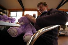 "A woman sews the back of a ""Bobbie Bear"", a lavender and wheat stuffed soft toy, at the headquarters of Tasmania's Bridestowe Lavender located near the town of Nabowla, on the outskirts of Launceston June 4, 2014.  REUTERS/David Gray"