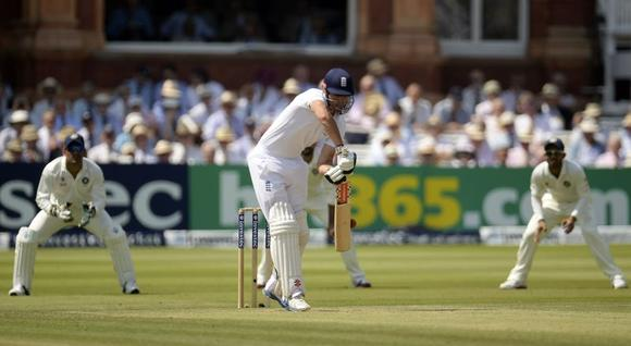 England's Alastair Cook edges the ball before being caught by India's Mahendra Singh Dhoni (L) for ten runs during the second cricket test match at Lord's cricket ground in London July 18, 2014. REUTERS/Philip Brown