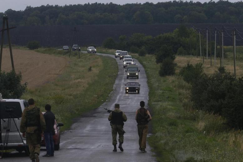 Pro-Russian separatists watch as Organisation for Security and Cooperation in Europe (OSCE) monitors arrive at the crash site of Malaysia Airlines flight MH17, near the settlement of Grabovo in the Donetsk region, July 18, 2014.  REUTERS/Maxim Zmeyev