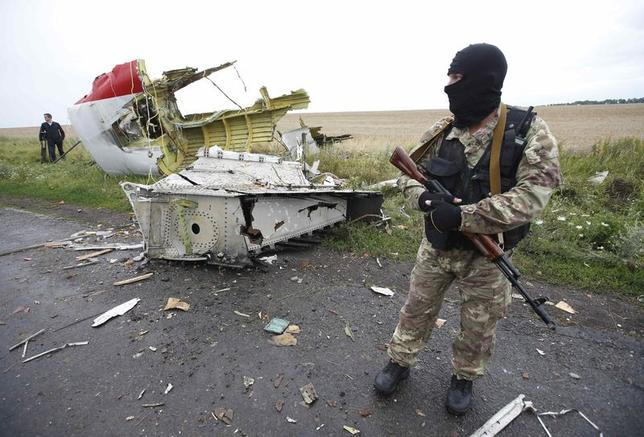A pro-Russian separatist stands at the crash site of Malaysia Airlines flight MH17, near the settlement of Grabovo in the Donetsk region, July 18, 2014. REUTERS/Maxim Zmeyev