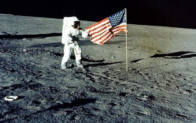 Charles ''Pete'' Conrad Jr. stands with the U.S. flag on the lunar surface during the Apollo 12 mission, in this 1969 file photo. REUTERS/NASA/Handout