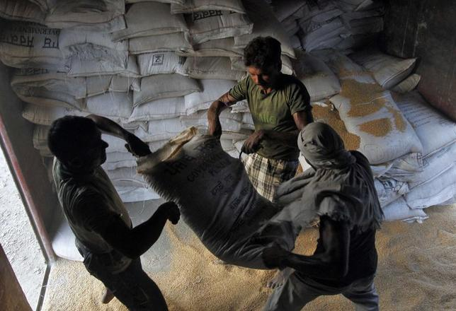 Labourers unload sacks of wheat from a goods train at a railway yard in Allahabad July 10, 2014. REUTERS/Jitendra Prakash/Files