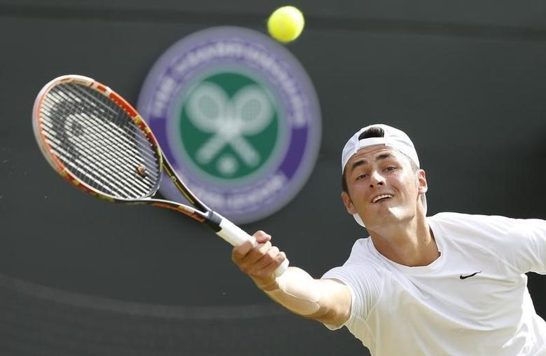 Bernard Tomic of Australia hits a return to Tomas Berdych of Czech Republic during their men's singles tennis match at the Wimbledon Tennis Championships, in London June 25, 2014.      REUTERS/Suzanne Plunkett