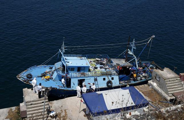Hazmat and forensic officers work on board a fishing boat, on which 19 migrants are reported to have died, at the Armed Forces of Malta (AFM) Maritime Squadron base in Valletta's Marsamxett Harbour, after it was towed to Malta by the AFM, July 20, 2014. REUTERS/Darrin Zammit Lupi