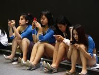 Un grupo de promotoras utilizan teléfonos móviles en una conferencia del mercado de telecomunicaciones en Pekín, mayo 6 2014. El número de internautas chinos que se conectan a la red a través de un dispositivo móvil - como un teléfono avanzado o tablet - ha superado por primera vez a aquellos que lo hacen con un ordenador personal (PC), dijo el lunes el Centro oficial de Información de Internet en China(CNNIC). REUTERS/Kim Kyung-Hoon