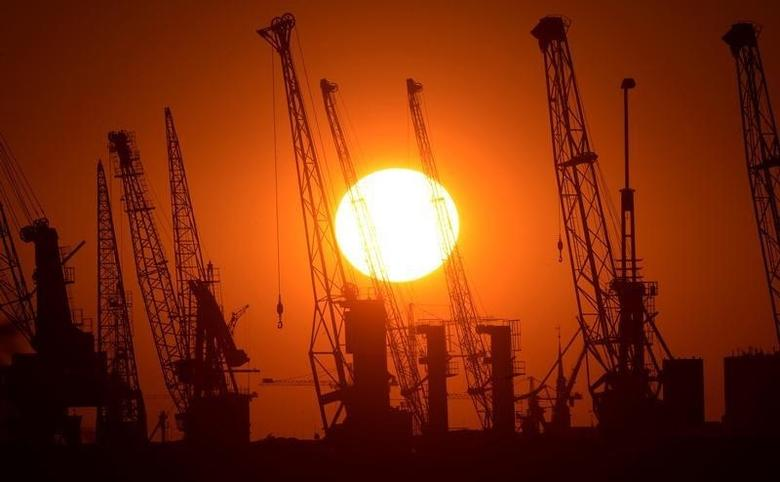 Cranes of German shipyard Blohm&Voss are silhouetted against the setting sun in Hamburg July 22, 2013. Picture taken July 22.  REUTERS/Fabian Bimmer