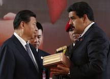 El presidente chino, Xi  Jinping, recibe un presenta de manos de su colega venezolano, Nicolás Maduro, en Caracas, jul 21 2014. Venezuela renovó el lunes una línea de crédito por 4.000 millones de dólares con China, como parte de la expansión de un millonario fondo de financiamiento conjunto para proyectos sociales y de infraestructura en el país sudamericano.   REUTERS/Carlos Garcia Rawlins