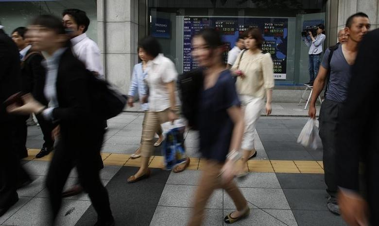 Pedestrians walk past at an electronic board showing the stock market indices of various countries outside a brokerage in Tokyo June 2, 2014. REUTERS/Yuya Shino