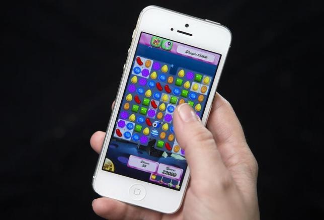 A woman poses for a photo illustration with an iPhone as she plays Candy Crush in New York February 18, 2014. REUTERS/Carlo Allegri/Files