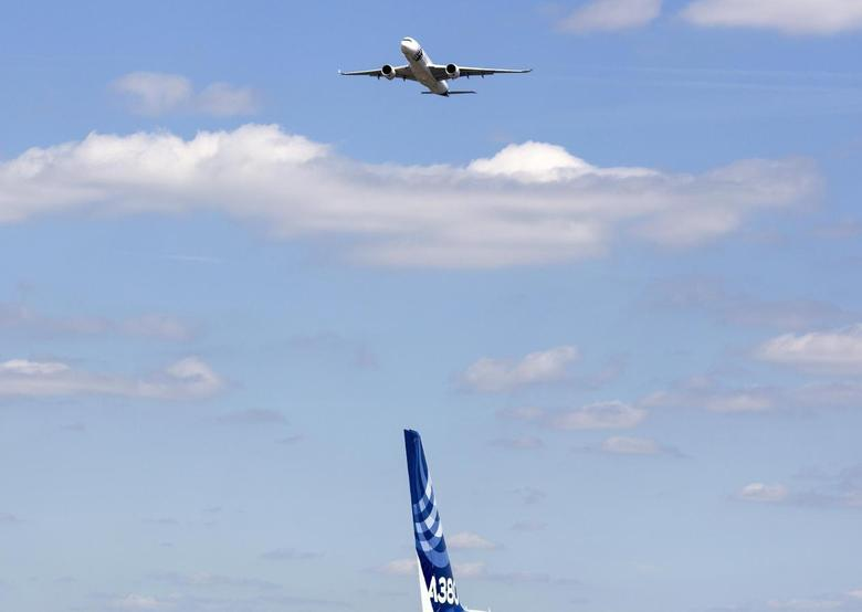 The Airbus Industrie A350 aircraft performs a manoeuvre above the A380 tail fin during its display at the 2014 Farnborough International Airshow in Farnborough, southern England July 14, 2014.    REUTERS/Kieran Doherty