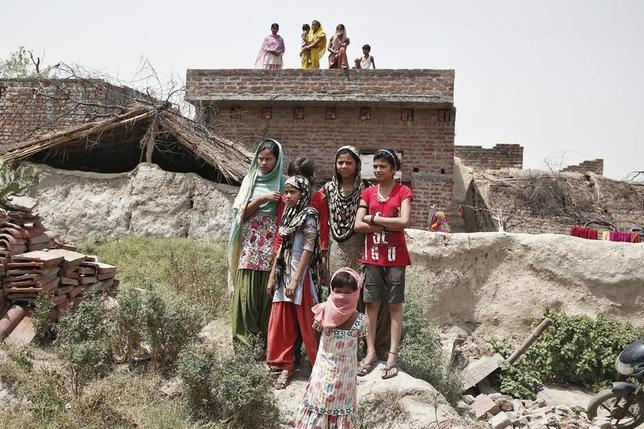 Villagers stand as they watch the house of one of the two teenage girls, who were raped and hanged from a tree, at Budaun district in the northern Indian state of Uttar Pradesh May 31, 2014.  REUTERS/Anindito Mukherjee