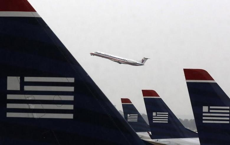 An American Eagle Embraer ERJ-140LR jet takes off as U.S. Airways jets are lined up at Reagan National Airport in Washington July 12, 2013.  REUTERS/Larry Downing