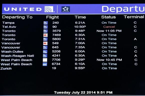 A United Airlines electronic departure board is pictured inside their terminal at Newark International Airport in New Jersey, July 22, 2014. REUTERS/Eduardo Munoz