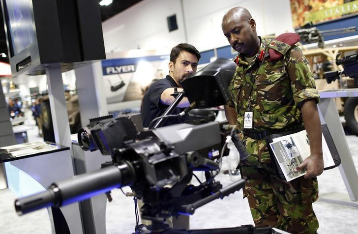 A representative from General Dynamics describes the benefits of their Next Generation Fire Control System to a military representative from Uganda inside the exhibit hall at the Special Operations Forces Industry Conference in Tampa, Florida, May 21, 2014.  REUTERS/Brian Blanco