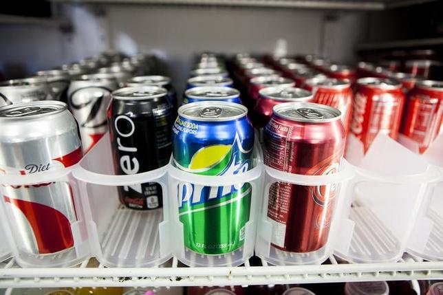 Cans of soda are displayed in a case at Kwik Stops Liquor in San Diego, California February 13, 2014. Sodas and most other sugar-sweetened drinks sold in California would be required to carry warning labels for obesity, diabetes and tooth decay under a bill introduced in Sacramento on Thursday and backed by several public health advocacy groups. REUTERS/Sam Hodgson (UNITED STATES - Tags: POLITICS FOOD HEALTH)