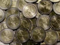 Монеты 2 евро на монетном дворе в Вене 20 июня 2013 года. Евро в четверг поднялся с восьмимесячного минимума благодаря индексу деловой активности в еврозоне, превысившему прогнозы, однако риски для экономики блока, которые может спровоцировать введение жестких санкций против России, ограничивают рост валюты. REUTERS/Leonhard Foeger