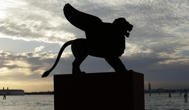 A statue of a lion, the symbol of the 69th Venice Film Festival, is silhouetted in Venice August 28, 2012. REUTERS/Tony Gentile/Files