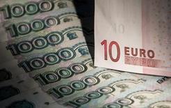 Купюры валют евро и рубль в Москвеy 17 февраля 2014 года. Рубль показывал отрицательную динамику на торгах четверга из-за рисков объявления Евросоюзом новых санкций против России, часть из которых может носить экономический характер. REUTERS/Maxim Shemetov