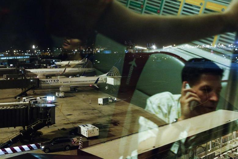 United Airlines planes are seen from the window of an airtrain as passengers are reflected in the glass at Newark International Airport in New Jersey, July 22, 2014. REUTERS/Eduardo Munoz