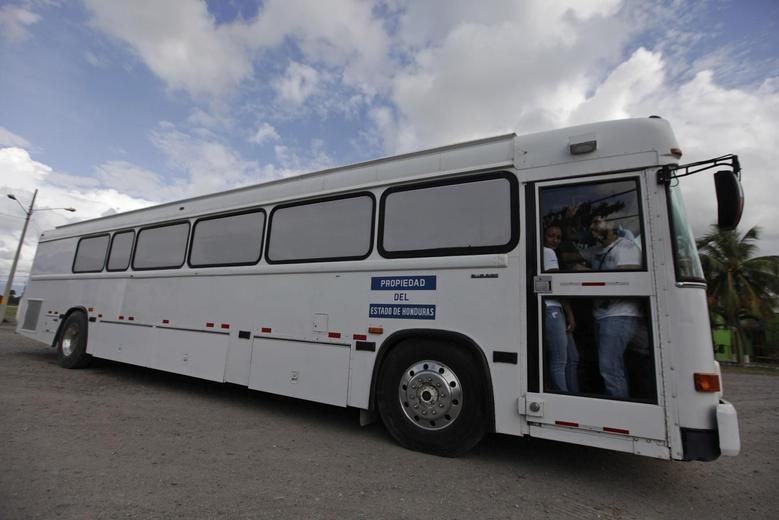 A bus carrying deportees from the U.S. leaves the international airport in San Pedro Sula, northern Honduras July 14, 2014. REUTERS/Jorge Cabrera