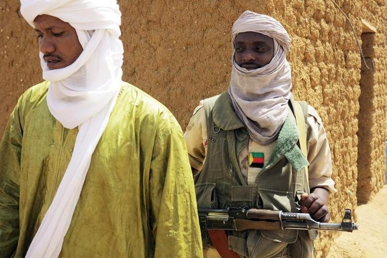 A fighter with the Tuareg separatist group MNLA (National Movement for the Liberation of Azawad) stands guard outside the local regional assembly, where members of the rebel group met with the Malian army, the UN mission in Mali and French army officers, in Kidal June 23, 2013.  REUTERS/Adama Diarra