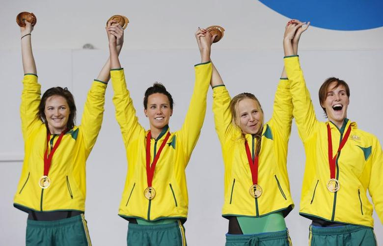 Australia's Cate Campbell (L), Emma McKeon (2nd L), Melanie Schlanger (2nd R) and Bronte Campbell celebrate after receiving their gold medals for the Women's 4x100m Freestyle at the 2014 Commonwealth Games in Glasgow, Scotland, July 24, 2014.  REUTERS/Suzanne Plunkett