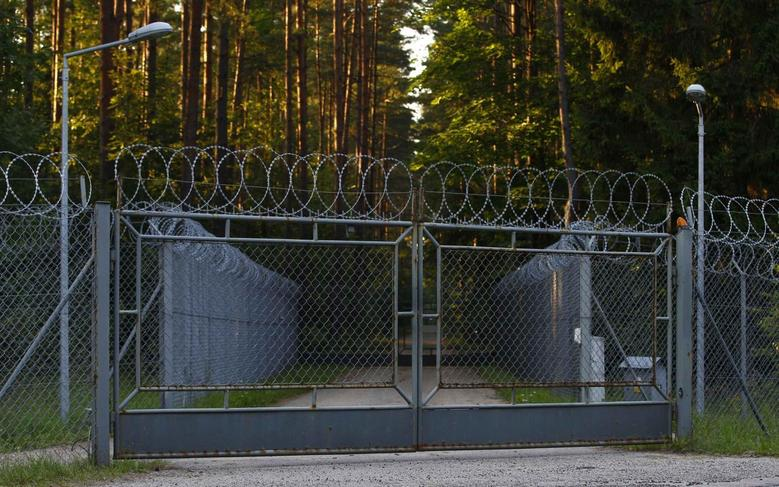 A barbed wire fence surrounding a military area is pictured in the forest in Stare Kiejkuty village in northeastern Poland, in this August 16, 2013 file photo. REUTERS/Kacper Pempel/Files